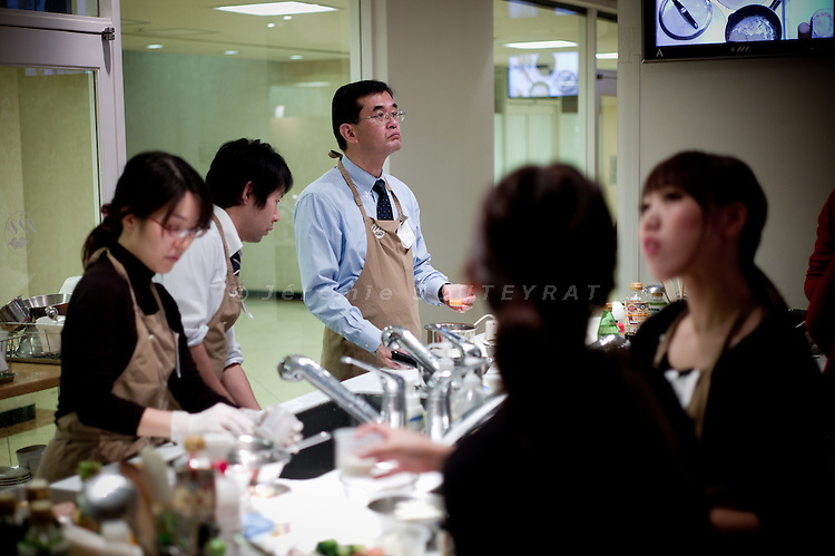 Tokyo, December 8 2010 - Japanese men and women having cooking lessons at ABC cooking studio in the Ginza area. More and more men have cooking lessons in Japan.