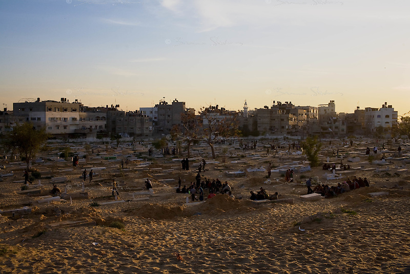 Beit Lahia, Gaza Strip, Jan 15 2009.Mourning families gather over hundreds of fresh tombs in Beit l-Lahia's main cemetery..