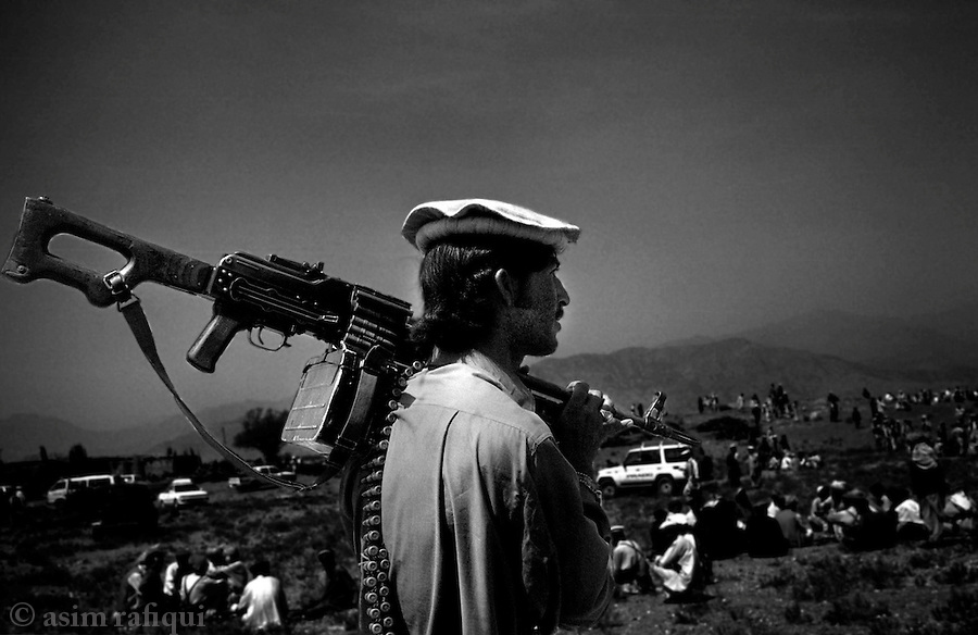 barwaiz raghzai hills, south waziristan, april 2004: members of the ahmedzai wazir gather for a tribal lashkar laden with heavy weapons.  the lashkar was called to track down and evict suspected al qaeda fighters and their collaborators thought to be hiding in the mountains bordering pakistan and afghanistan.<br />
