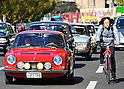 November 27, 2011, Tokyo, Japan - A 1967 French Simca 1200s Coupe goes abrest with a cyclist during the fifth Classic Car Festa 2011 in Tokyo on Sunday, November 27, 2011. Some 43,000 spectators watch about 100 domestic and foreign classic and vintage cars parade the gingko-lined streets of the Meiji Shrines Outer Garden in the annual open-air exhibition and parade sponsored by Toyota Automobile Museum. (Photo by Natsuki Sakai/AFLO) [3615] -mis-