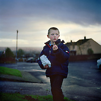 A young boy in Ballysillan estate plants flower bulbs as part of the final re-imaging effort in the area. Re-imaging areas with violent and intimidating reminders of the past has been a struggle for members of the Ulster Defence Association (UDA). In Ballysillan many locals that the removal of traditional murals would mean having their culture and memories stripped away. After careful deliberation and discourse, new sculptures, murals and gardens have been designed and installed by residents.