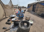 A woman from Darfur cooks a meal in the Goz Amer refugee camp in eastern Chad. More than a quarter million residents of Darfur live in camps in Chad, along with almost 200,000 Chadians who have been internally displaced by related violence.