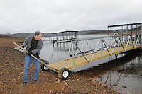 NWA Democrat-Gazette/FLIP PUTTHOFF <br /> Beaver Lake is generally, but not always, at its lowest level during winter. A rise or fall in the level impacts dock owners and boaters, even drinking water providers such as the Beaver Water District. Rick and Mary Loots move their dock into deeper water on Jan. 11 in the Rocky Branch area.
