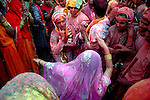 A man dances with a lady during lathmar holi. Song and dance are part of lathmar holi festival. The lyrics of the songs generally have sexual connotation, which makes the girl angry. As holi itself is played among men and women but only in Barsana holi is still celebrated in the way its written in the epics. Barsana, Uttarpradesh, India