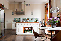 General view of the spacious kitchen-diner which combines contemporary functionality with the period features of the apartment and retro furniture