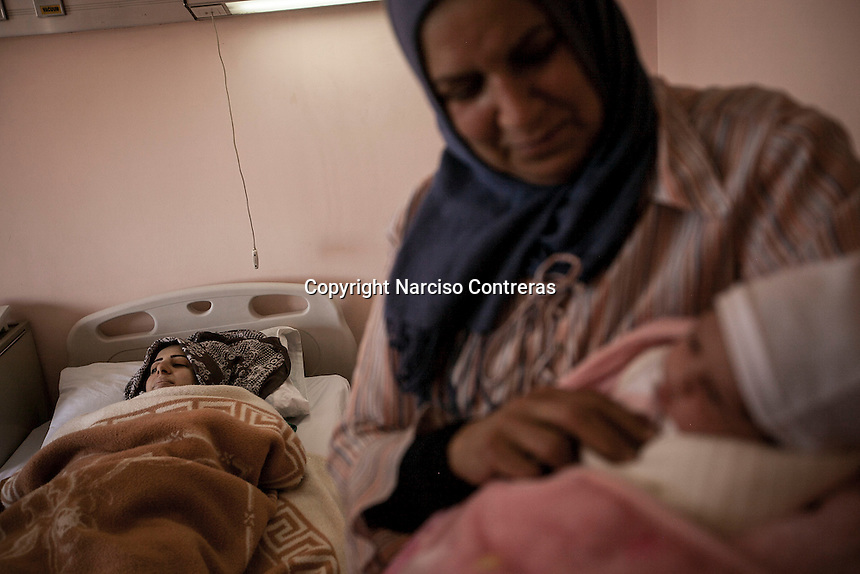 June 11, 2015 - Bekaa Valley, Lebanon: A Syrian woman from Damascus lays on a bed after gave birth to his two hours new born baby held on arms by his grandmother in a maternity ward at Rahme hospital in Taanayel city in east of Lebanon. The baby as many like him with Syrian roots was born stateless after their parents fled years ago from their hometowns in Syria when opposition armed groups started battling against the government of President Bashar Al-Assad. (Photo/Narciso Contreras)