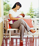 Mother breastfeeding baby while sitting on bench