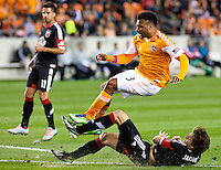 Giles Barnes of the Dynamo, goes air borne over the slidetackling Dejan Jakovic of D.C United at BBVA Compass Stadium. Houston beat D.C United, 2-0 in the MLS season opener.