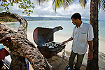 Local Dominican man grills potatoes and fresh fish on Playa Bonita and Coson, Samana, Domincan Republic