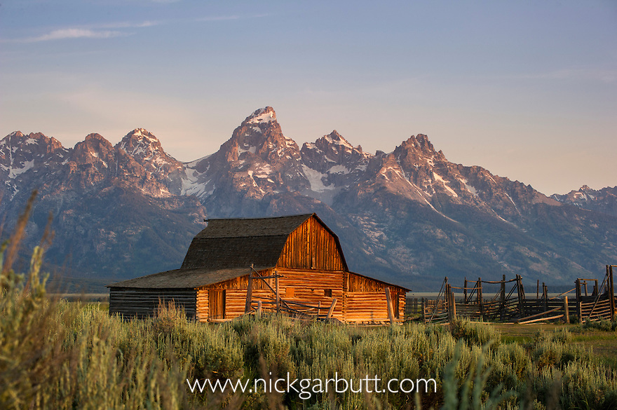 The John Moulton Barn at sunrise. On Mormon Row, Antelope Flats, Grand Teton National Park, near Jackson Hole, Wyoming. With Grand Teton mountain range in the background.