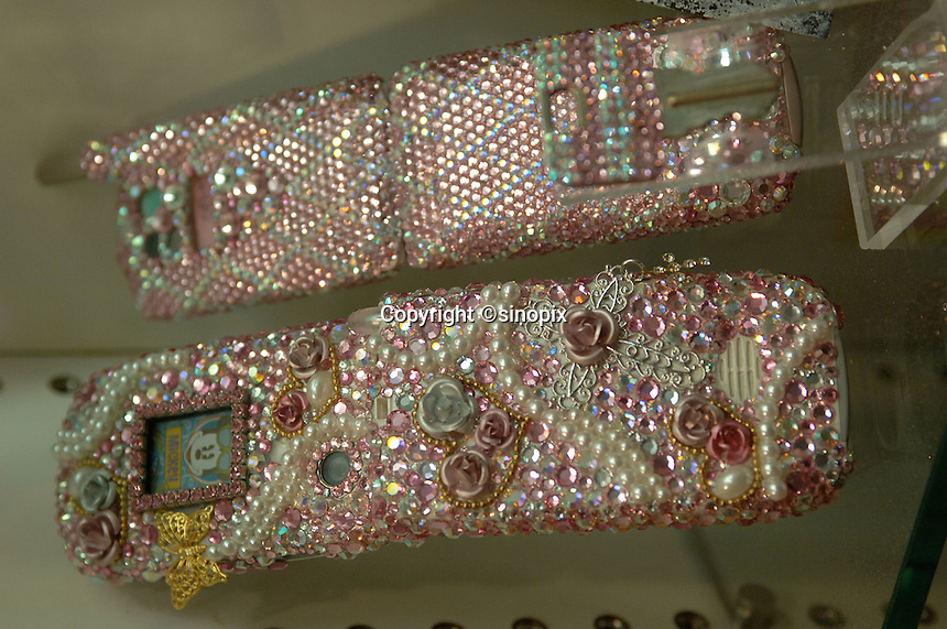 A shop specialises in the customising of the exterior of mobile phones to go hand in hand with the fashion of sparkling jewellery and gemstones on clothes and finger nails in Tokyo, Japan. .