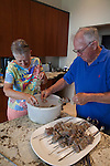 A senior couple prepares food for a barbeque at their home on Sanford Lake, Michigan, USA