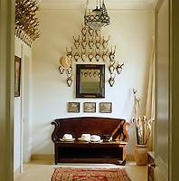 A collection of inscibed hunting trophies line the wall of this entrance hall which features an antique bench