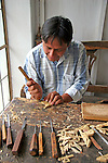South America, Ecuador, San Antonio de Ibarra.  Woodcarver at work in his studio in San Antonio de Ibarra, in the Ecuadorian Andes.