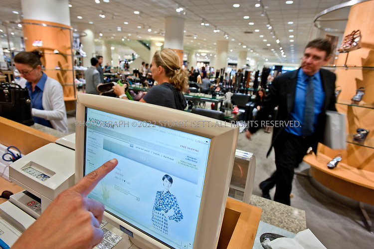 8/19/2010--Seattle, WA, USA..Staff inside Nordstrom's Seattle flagship store, staff use a touchscreen panel at the cash register to check online for available merchandise. Through the  panel screen staff can access Nordstrom website and inventory control to better serve their customers..Nordstrom's corporate headquarters and flagship store are located in Downtown Seattle, Washington. Nordstrom has grown from a regional department store to a national chain by opening new stores rather than by acquisition of other retailers. Nordstrom operates 112 full-line department stores, 68 Nordstrom Rack clearance stores, including one in New York City...©2010 Stuart Isett. All rights reserved.