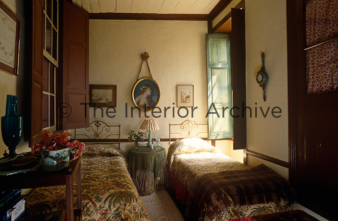 A pair of chintz quilts covers matching wrought-iron twin beds and old-fashioned shutters screen the windows in a twin-bedroom of a traditional house in the Canary Islands