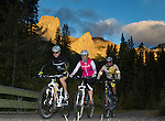 Mountain bikers Matt Hadley (left), Tricia Wilson (right) and Stefan Grecu (center) are biking together at the Canmore Nordic Centre in Canmore, Alberta, Canada.