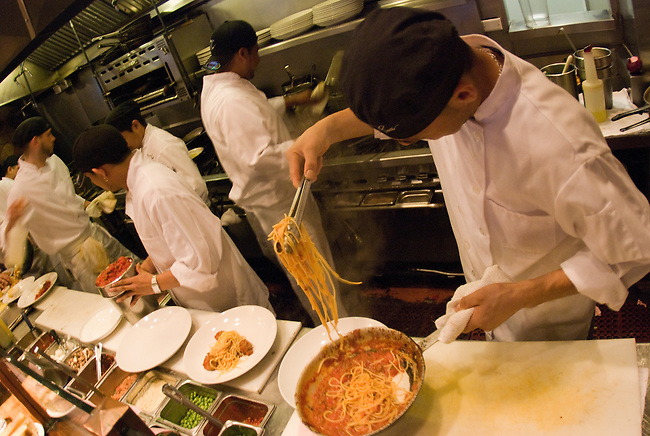 Cooks work to prepare meals in a restaurtant in San Francisco