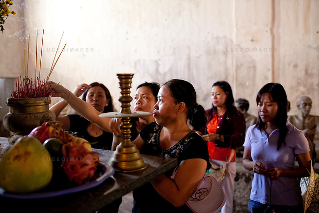 Tourists guide burns incense at an alter in memory of those who died at  Phu Hai Prison on Con Son Island, part of the Con Dao Islands.The 16 mountainous islands and islets are situated about 143 miles southeast of Ho Chi Minh City in Vietnam, in the South China Sea. Phu Hai Prison, which was built in 1862, is the largest and oldest prison on Con Son Island.  Eleven prisons were built on the island and are now open for tours.  Photo taken Thursday, May 5, 2010...Kevin German / LUCEO For the New York Times