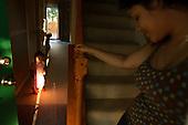 Immigrant from Honduras Elsie Savalba, 25 and her daughter Alison,1  at their foreclosed home. Its price went down from 295 thousand dollars to 150 thousand within one year. Alison has not been paying her mortgage for last 6 months. .They will be moving out soon.This area has been badly hit by crisis in property market. Lots of houses are foreclosed or abandoned. Value of many properties here has dropped by half within one year.  Manassas, June 2008.<br /> (Photo by Piotr Malecki / Napo Images) <br />  <br /> Emigranta z Hondurasu, Elsie Savalba i jej corka Alison w domu przejetym przez bank. Wkrotce beda musieli sie wyprowadzic, ale nie wiedza jeszcze dokad.W ciagu roku wartosc ich domu spadla z 295 tys $ do 150 tys $, wiec nie maja jak splacic pozyczki.Polnocna Wirginia, a szczegolnie Prince William County jest jednym z najmocniej dotknietych kryzysem nieruchomosci miejscem w Stanach Zjednoczonych. Setki tysiecy domow sa opuszczane przez wlasciecieli bez widokow ani na ich sprzedaz ani na splate zaciagnietego kredytu.Manassas, Wirginia, USA Czerwiec 2008.<br /> (Photo by Piotr Malecki / Napo Images)  .