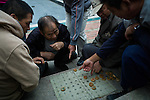 Men are playing xiangqi, a Chinese variation of chess, in a park in the old town of Qingdao.