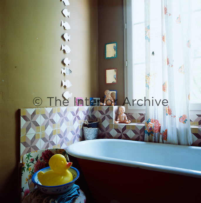 The bathroom has a traditional, yet eclectic, feel with mustard coloured walls and a Victorian style freestanding roll top bath