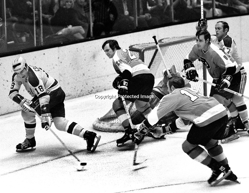 Seals vs Flyers, Gary Croteau chasing puck, Flyers .Wayne Hillman, Larry Hale,Larry Mickey,  Frank Spring, Flyer goalie Bruce Gamble..(1971 photo/Ron Riesterer)