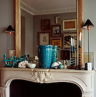 A gilt mirror hangs above a traditional fireplace in the living room