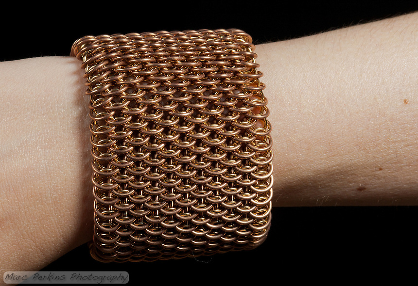 "A brass and bronze dragonscale weave chainmail bracelet seen on a pale-skinned arm up close.  The maille was made with 18ga 1/4"" bronze and 19ga 11/64"" jeweler's brass, and uses a gold tone slide clasp.  The view emphasizes how the flexible weave looks very different depending on the angle it's view from."