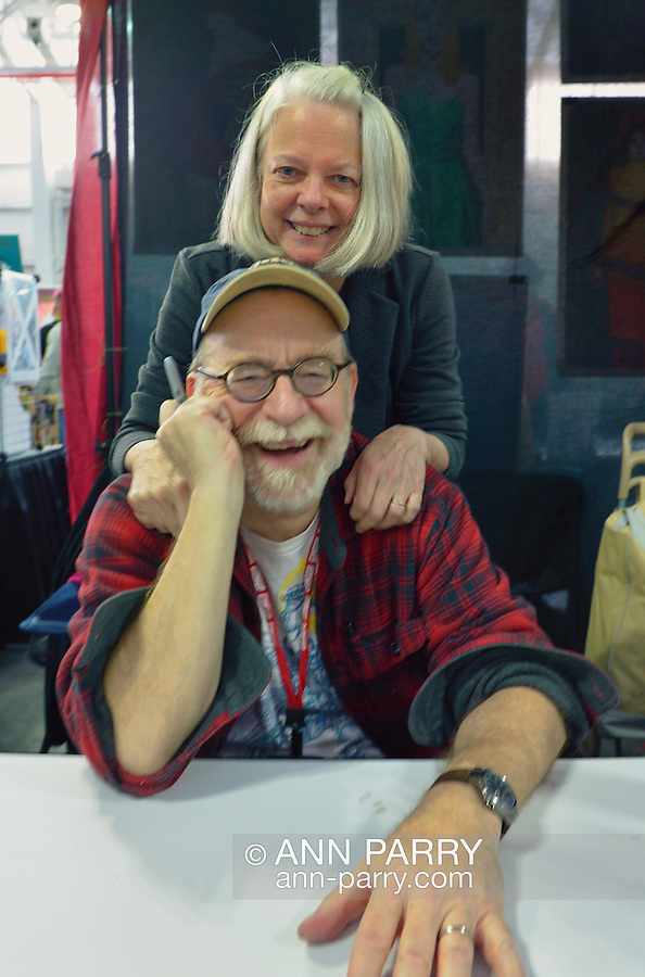 Manhattan, New York City, New York, USA. October 10, 2015. LOUISE SIMONSON, a Marvel Comics writer, smiles as she poses with her husband WALT SIMONSON, a Marvel pencil artist, who shakes with laughter, at Artist Alley at the 10th Annual New York Comic Con. They each were available to sign their action hero comic books at NYCC 2015, expected to be the biggest one ever, with over 150,000 attending during the 4 day ReedPOP event, from October 8 through Oct 11, at Javits Center in Manhattan