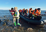 A Norwegian volunteer carries a small boy to shore as refugees land on a beach near Molyvos, on the Greek island of Lesbos, on November 3, 2015, after crossing the Aegean Sea from Turkey. Local and international volunteers welcomed the arriving refugees with food and medical care and dry clothes before the newcomers proceeded on their way toward western Europe. Their boat to Greece was provided by Turkish traffickers to whom the refugees paid huge sums to arrive in Greece.