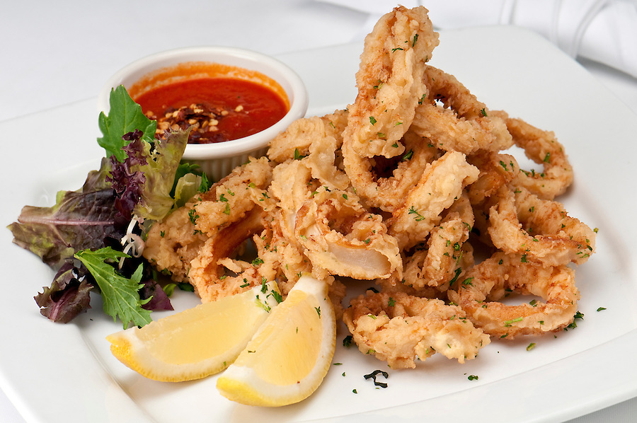 Plate of fried calamari served with marinara sauce and lemon.