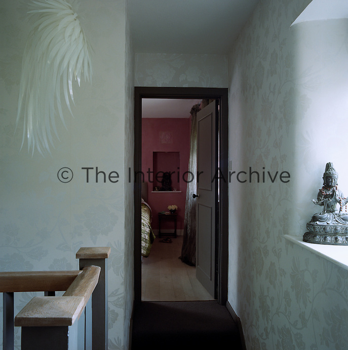 Silvery embossed paper lines the walls of an upstairs landing where a bedroom can be seen through an open door