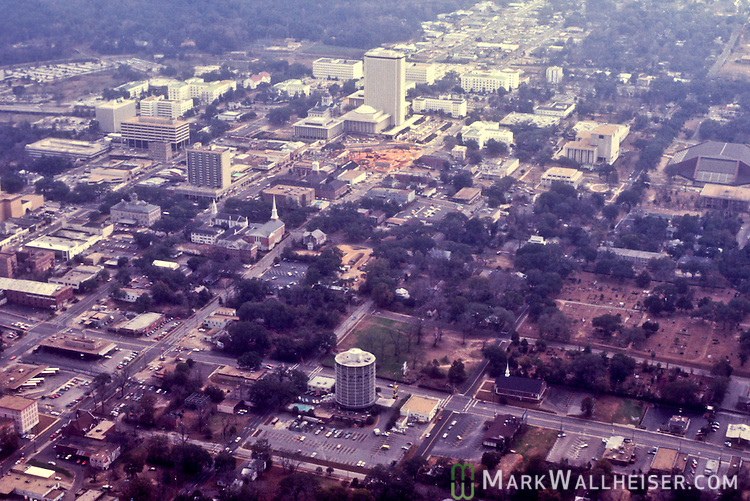 1981 Historical aerial photographs of the old round Holiday Inn (foreground) and downtown Tallahassee, Florida December 23, 1981. The brown dirt to the north of the Capitol is Tallahassee City Hall under construction