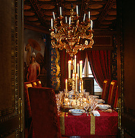 A Louis XIV Genoese giltwood chandelier in the dining room hangs above a table covered in a red silk damask