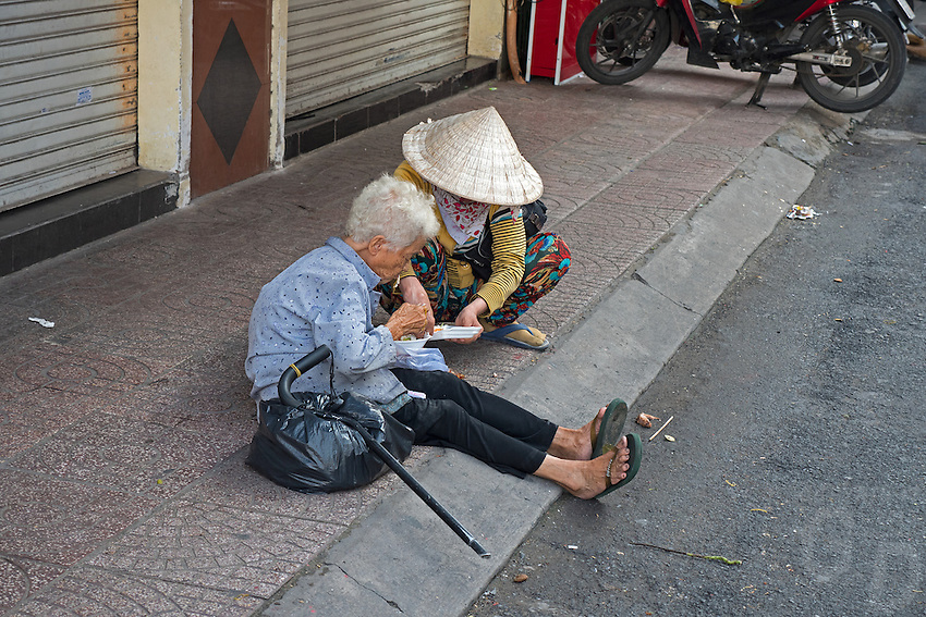 Feeding the old in the streets of Saigon or in Vietnamese Ho Chi Minh City where old and new architecture mix in harmony. The bustling Metropolis of South Vietnam.