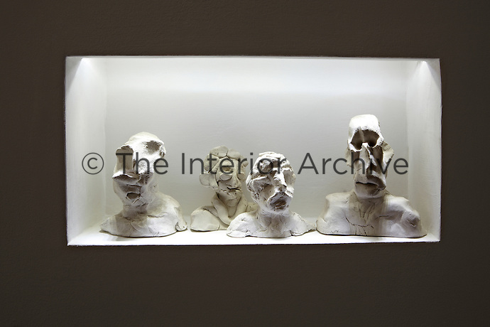 Contemporary sculptures of heads are displayed in a lit recessed niche