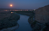 A full moon sets over the San Juan river as it winds past Farmington, N.M., Thursday, July 1, 2004. Many members of the Navajo nation don't have running water due to the remoteness of their homes. Thanks to the ongoing drought in the west and New Mexico's renegotiation of water treaties, many of these people may be conected to the water mains for the first time. (Kevin Moloney for the New York Times)
