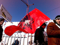 Three young gentlemen and an Albanian flag passing the site of Pristina's new Catholic Cathedral on their way to the city centre to join the celebrations.