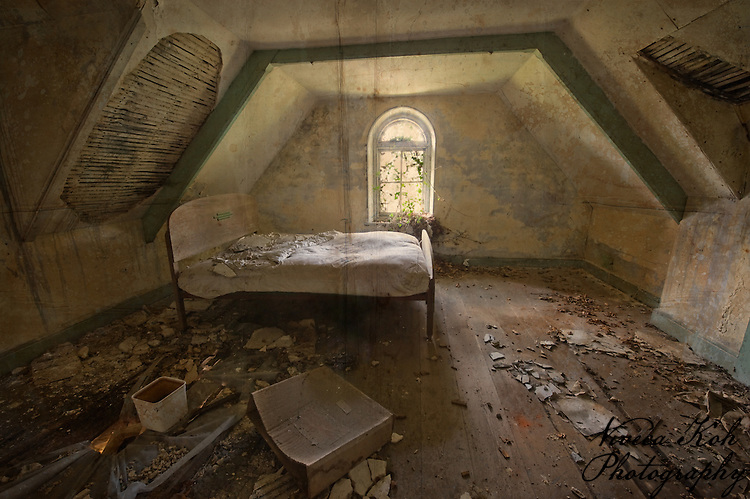 Bed in an attic room of abandoned manor house