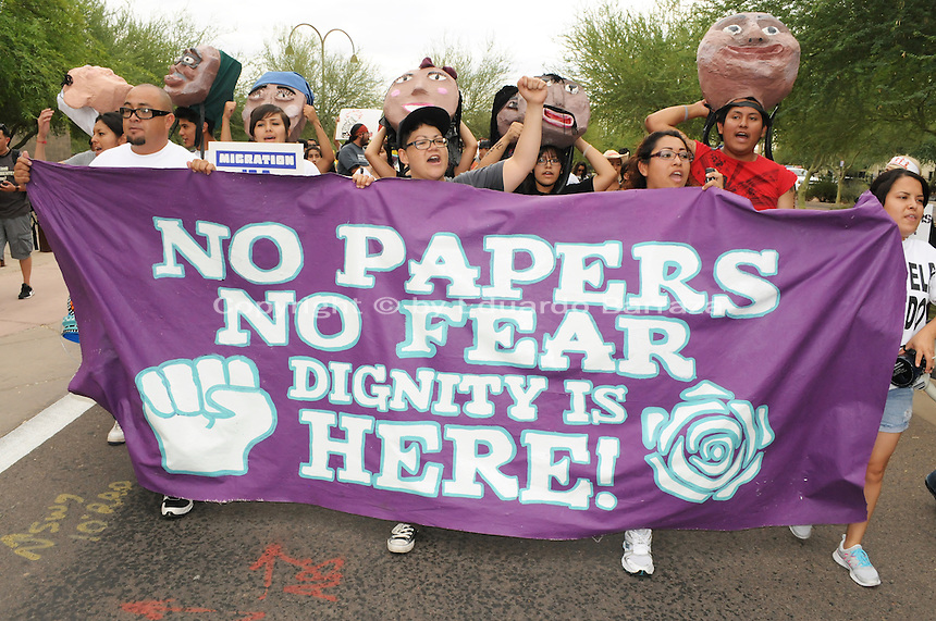 """Phoenix, Arizona (July 28, 2012) - About three hundred people marched to protest the second anniversary of the approval of some provisions of the SB 1070 immigration law. The march, called """"No Papers, No Fear"""" was organized by immigrant rights groups who say the law discriminates people of brown skin. In this photograph, protesters and undocumented immigrants (from left) Miguel Guerra, Isela Meraz, Leticia Ramirez, and Natally Cruz, hold a banner as the """"No Papers No Fear"""" march begins in Phoenix. All four protesters were arrested for civil disobedience acts on July 24 for blocking a major intersection in Downtown Phoenix. Photo by Eduardo Barraza © 2012"""