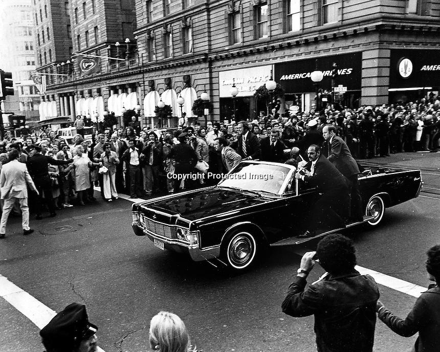 Secret Service agents jump on Limo and roar away from outside the St. Francis Hotel in San Francisco where Pres. Gerald Ford was shot at. .(copyright 1975 by Ron Riesterer)