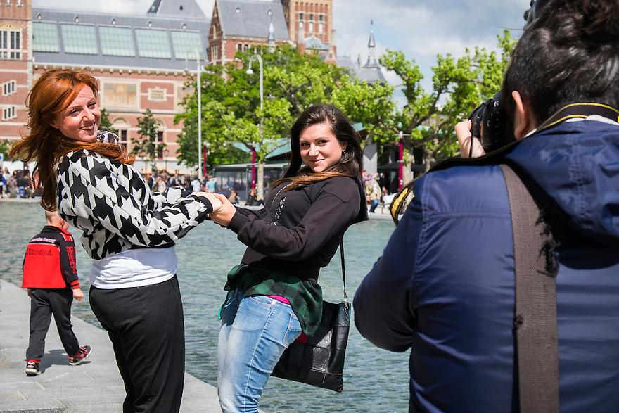 Nederland, Amsterdam, 30 mei 2015<br /> Jonge toeristen poseren en laten zich door vriend fotograferen op de rand van de vijver op het Museumplein pal voor het Rijksmuseum. <br />  <br /> Foto: Michiel Wijnbergh
