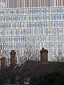 New glass office block being constructed near some very old brick houses in South East London.