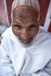 Portrait of an old muslim man, wearing a traditional white djellaba, in the old medina of Marrakech / Marrakesh, Morocco. Model released.