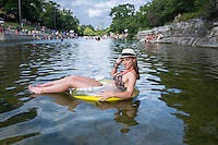 Fit sexy Austin girl floating on raft at Barton Springs Pool.