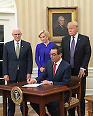 United States Treasury Secretary Seven Mnuchin signs confirmation paperwork as he is flanked by President Donald Trump (R), Vice President Mike Pence and his fiancee Louise Linton, after being swon-in as Treasury Secretary, during a ceremony at the White House in Washington, D.C. on February 13, 2017. Mnuchin was confirmed by the Senate 54-47. <br /> Credit: Kevin Dietsch / Pool via CNP