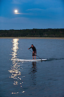 A stand up paddleboard paddler goes for an evening paddle under a full moon on Lake Superior at Grand Marais Michigan.