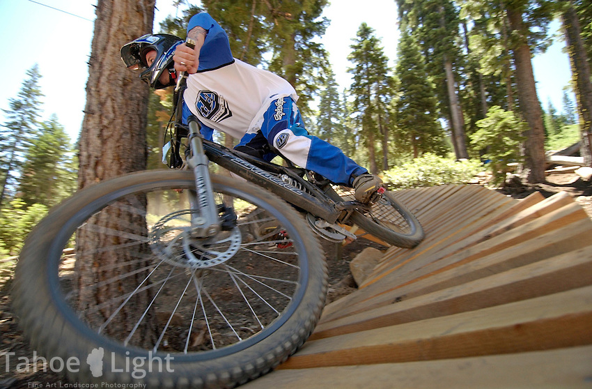 Reno freerider Jason Blanchard rides an elevated banked bridge on a trail at the mountain bike park at Northstar at Tahoe.
