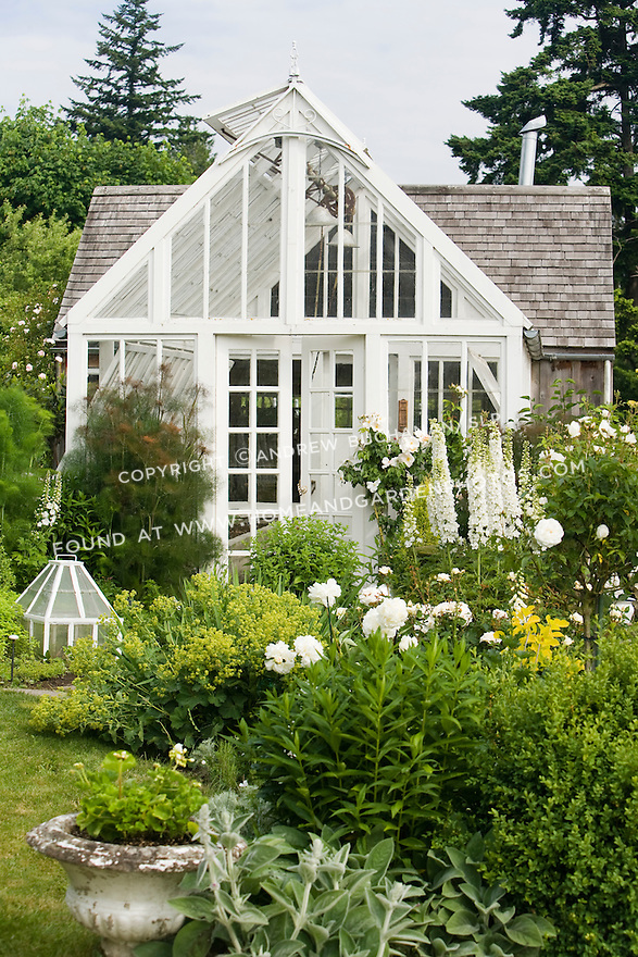 This white-painted greenhouse was salvaged from a local arboretum and restored for use here, and adds to the romantic, cottage garden feel of the Sissinghurst-style white garden behind the late 19th c. farmhouse on this property.  The garden also includes white peonies and delphiniums, white roses, and garden flox, among others. Garden design by Toni Christianson, Christianson's Nursery